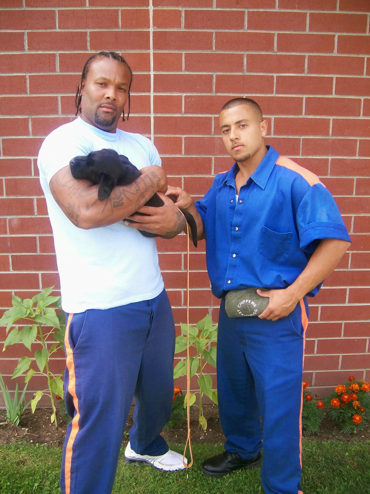 "An african american man (left), wearing a white t-shirt and blue prison pants, and a shorter man (right) wearing the blue prison uniform, stand in front of a brick wall. The african american man is cradling a small black lab puppy in his arms and the man beside him is resting his right hand on the puppy. This man's left hand is at his waist. Both men are peering at the camera with a ""tough guy"" gaze."