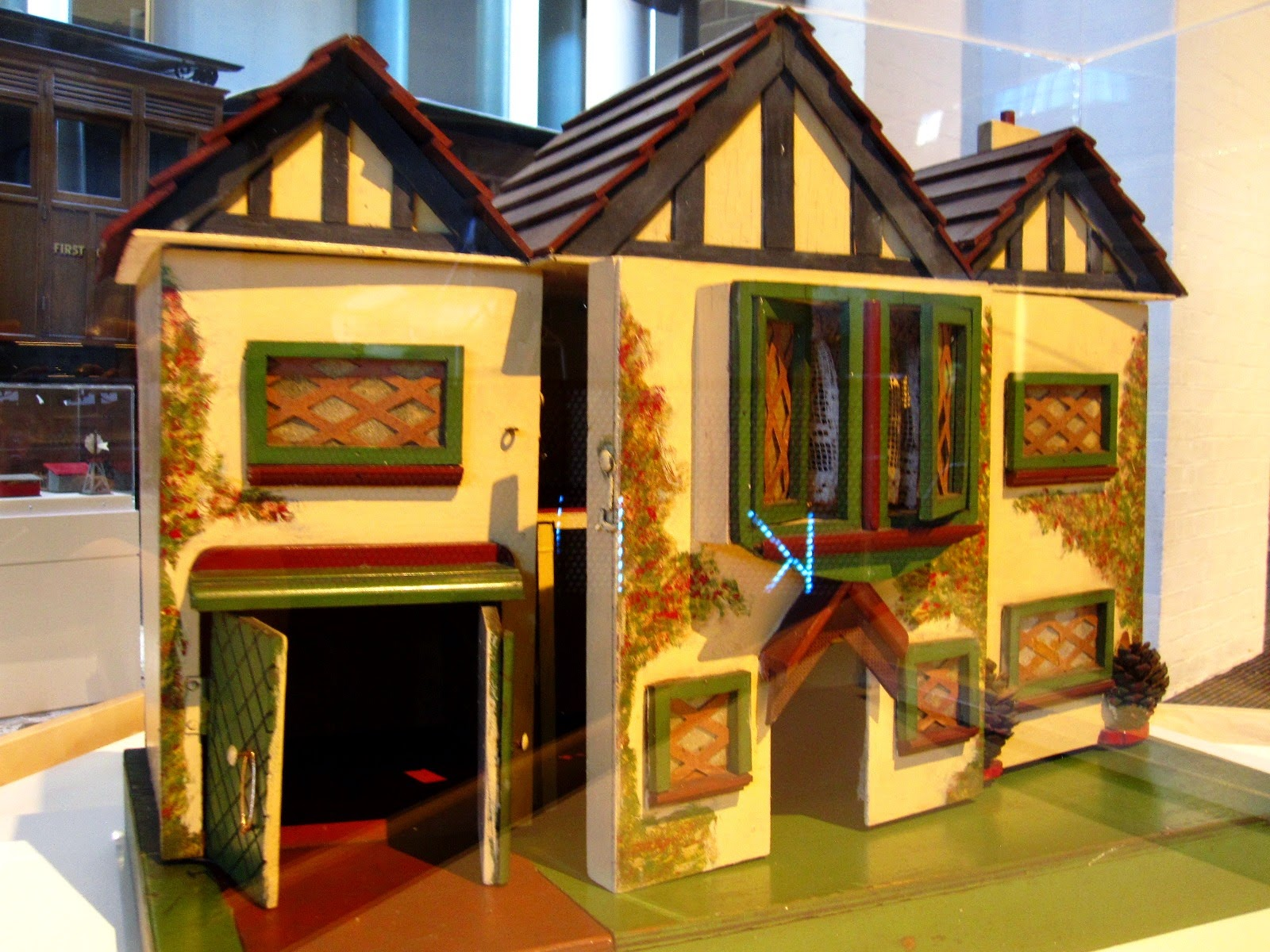 Front view of a vintage doll's house displayed in a museum.