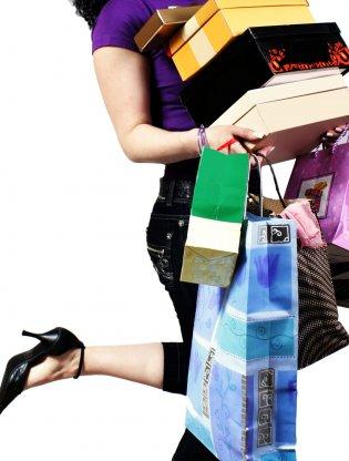 Žena nosi u rukama gomilu kutija i kesa iz kupovine gaderobe