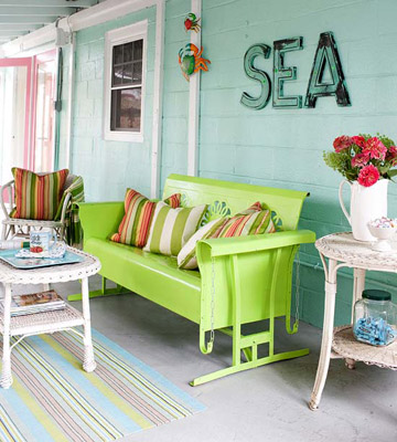 The costal turquoise colors of the house and lime green bench are stunning pops of color on this otherwise muted front porch