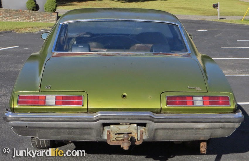 Fuel filler is below bumper and behind tag on 1973 Pontiac Grand Am and Grand Prix,