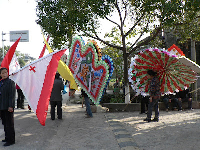 flags carried in funeral procession with a Christian cross