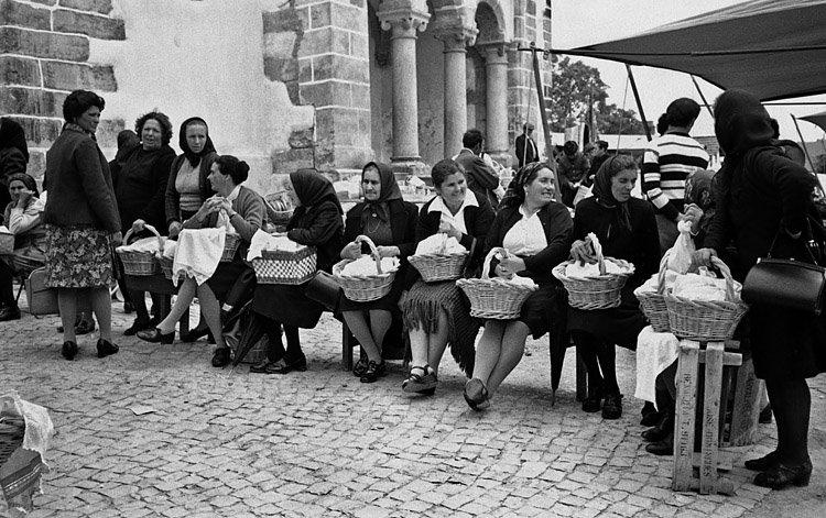 Vendedeiras apresentando produtos de confecção artesanal. Foto a preto e branco