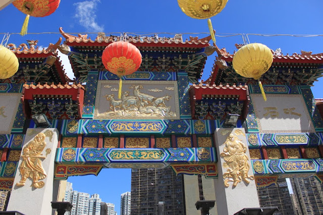 Admiring at beautiful sculptured pictures in gold on the archway at Wong Tai Sin Temple in Kowloon, Hong Kong
