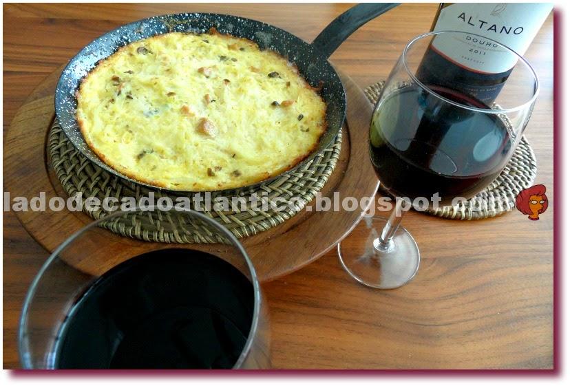 Imagem de fritada numa frigideira de ferro, das taças com vinho tinto e uma garrafa de vinho tinto