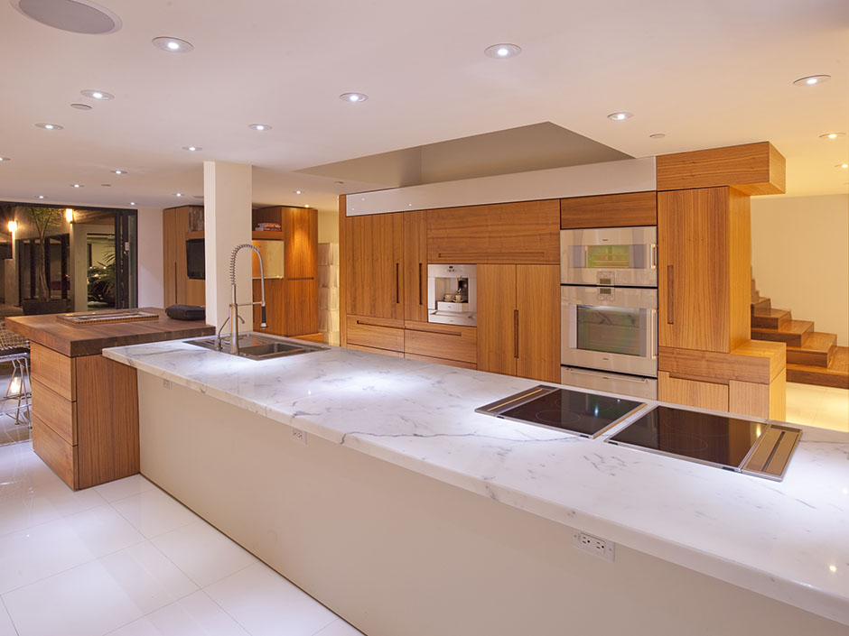Photo Of Wooden Furniture In The Kitchen Along With Huge Island Marble Surface