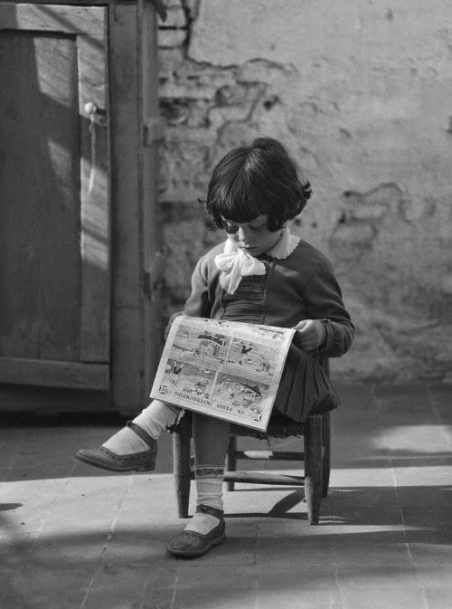 Noia petita llegint uns còmic seguda en una cadireta.