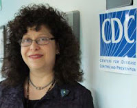 a plump middle-aged white woman with fluffy permed black hair and wire rimmed glasses stands next to a sign for the Centers for Disease Control