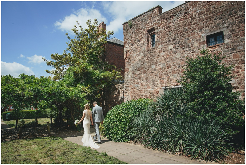 Bride and groom walking outside St Nicholas Priory Exeter
