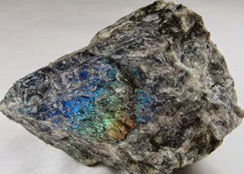 Bongkahan batuan mineral labradorit feldspar yang belum diolah dengan warna batu umumnya berwarna abu-abu hingga gelap dengan kombinasi warna cerah pada bagian dalamnya.
