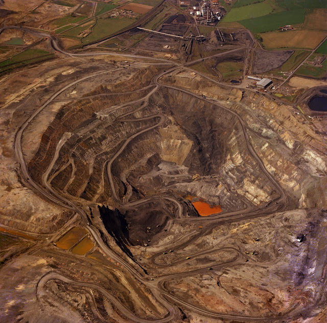 Oblique aerial view of the Westfield Opencast Coal Mine from the north-east Fife Region. Cut to extract the abnormally thick development of coals (Boglochty Beds) in the Passage Group of the Namurian of the Scottish Carboniferous succession. The excavation is about 200 metres deep and has cut through strata from just above the top of the Middle Coal Measures (Westphalian B) down to the Calmy Limestone of Namurian (E2) age. At the top are the processing plants. The Westfield Open Pit was worked by Costain Mining Limited on behalf of the National Coal Board Opencast Executive.