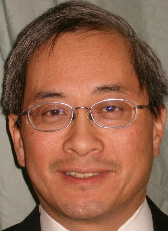 Head shot of Richard Hom, OD, MPH. He is facing forward, wearing glasses, and smiling