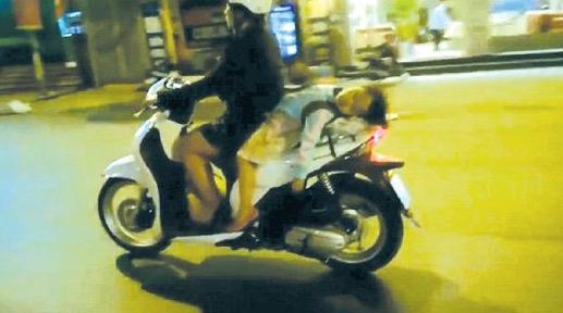 Budak tidur terlentang atas skuter yang ditunggang ibunya