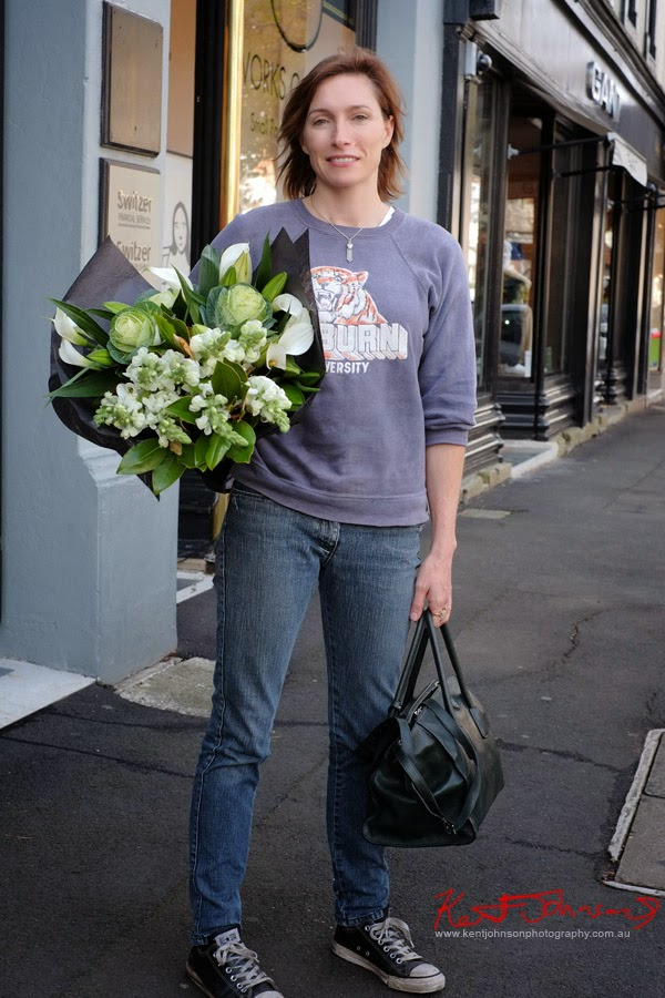 Claudia Karvan with bouquet of flowers, Sweatshirt, converse runners, Prada bag and vintage necklace; Olsen Irwin Works on Paper Gallery, Woollahra Sydney.