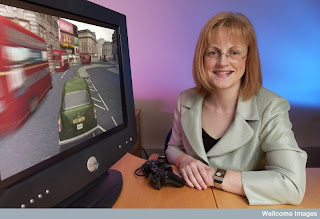 Eleanor Maguire with a video game that simulates driving a taxi through the streets of London