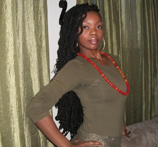 Pretty black girl with long dreads posing for a photo.