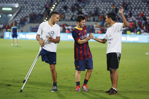 Lionel Messi speaks with two fans at the end of a training clinic with Arab and Jewish children