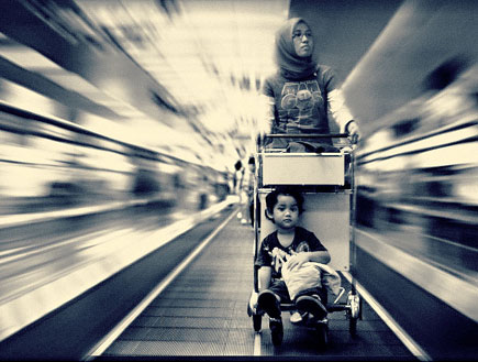 Black and white photo of a young lad being pushed on a trolly by his Mum on an airport travelator. Image by Julian Palapa.