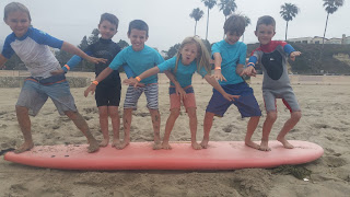 Six kids standing on a surfboard
