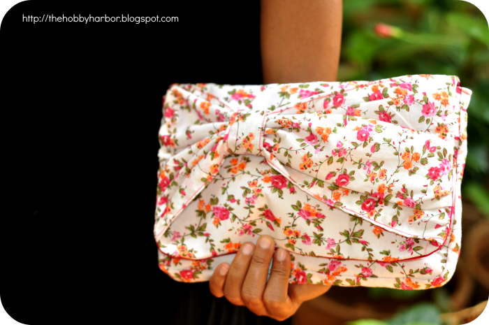 clutch or purse with bow on the front and floral print. Lot of pockets and handy. Handmade with pdf sewing pattern eve clutch by chris w design