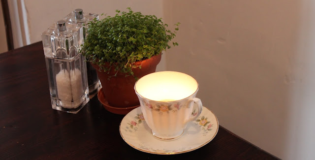 teacup candle and plant on table at Newbridge on Usk
