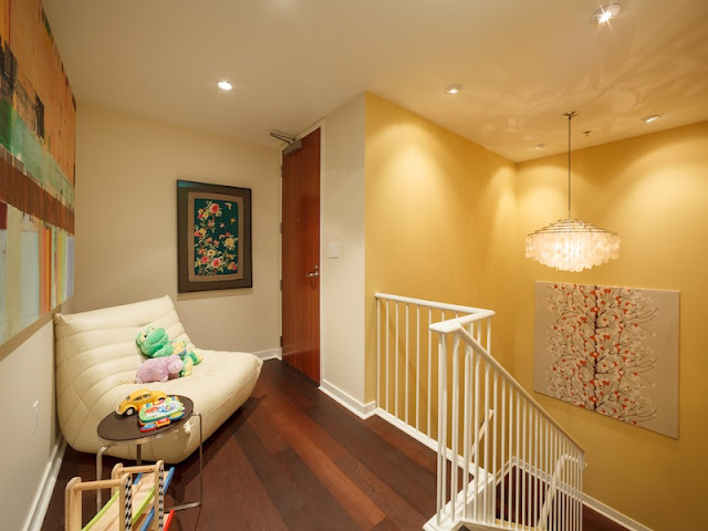 Picture of large white sofa and yellow walls on the upper level of duplex