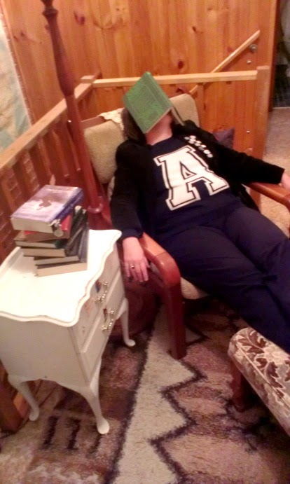 Woman 'asleep' in a reading chair, with her feet on a footstool and a book covering her face.