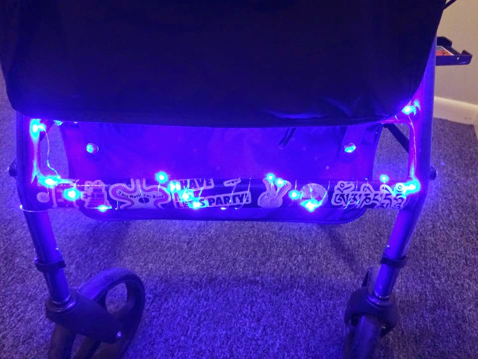 Photograph: A close-up of the font of a rollator walker. Wrapped around the front bar is a string of lights that are shining bright blue.