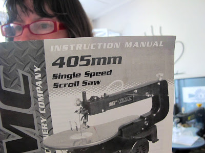Woman reading an instruction manual for a scroll saw.