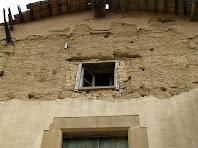 Detall de la façana principal en la que s'aprecia el material constructiu: pedra, calç, tàpia i maó, més embigat de fusta