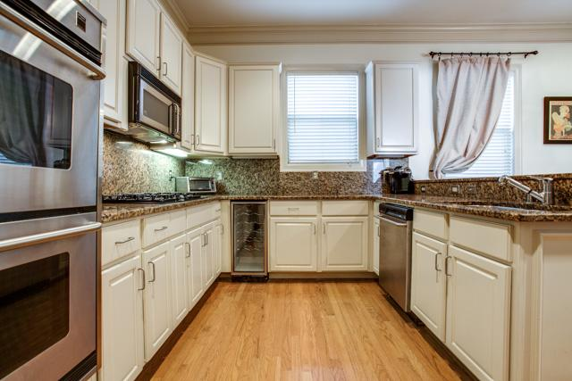 A Kitchen With Cream Colored Cabinets Stainless Steel Appliances Which Includes Double Oven And Gas Range Wine Frig As Well Dishwasher