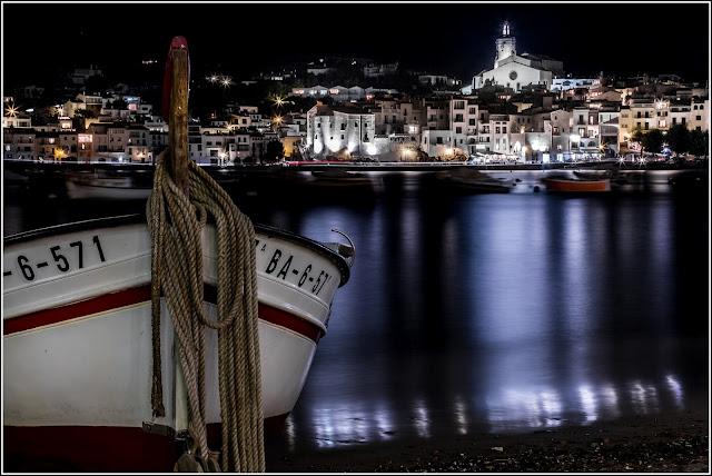 Cadaqués: Nocturna de la población con barca en primer plano
