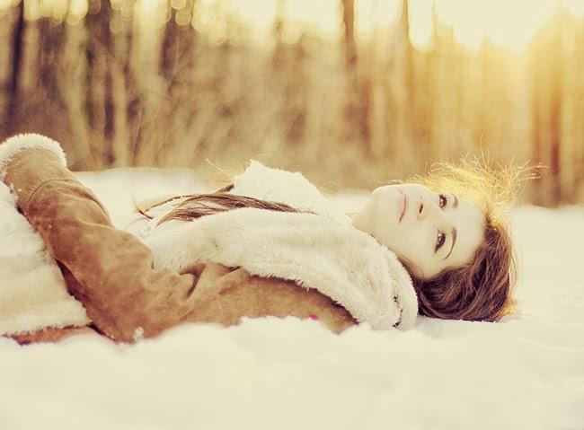 A girl lying on snow in lukewarm sunlight below the wide sky