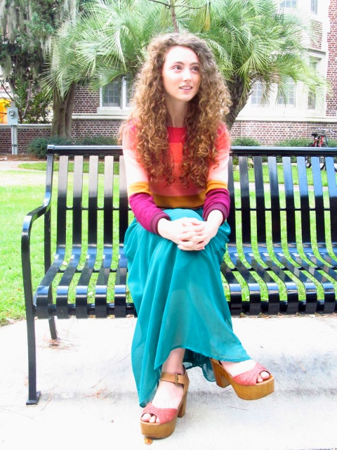 UF student Emily Moschner wears a colorful pink orange and purple layered sweater tucked into a  long double layered translucent teal dress grounded by a thin brown leather belt and bag. she is wearing brown and pink platform sandals and a brown scarf.