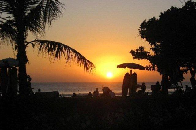 Atardecer, tablas de surf y palmeras. Playa Kuta Beach, Bali