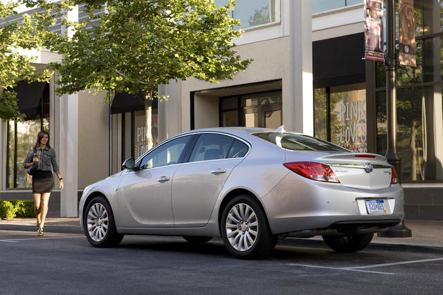 Silver 2012 Buick Regal E-Assist rear three-quarters view parked on city street with woman approaching