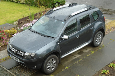 A shiny new Dacia Duster on the driveway to the left