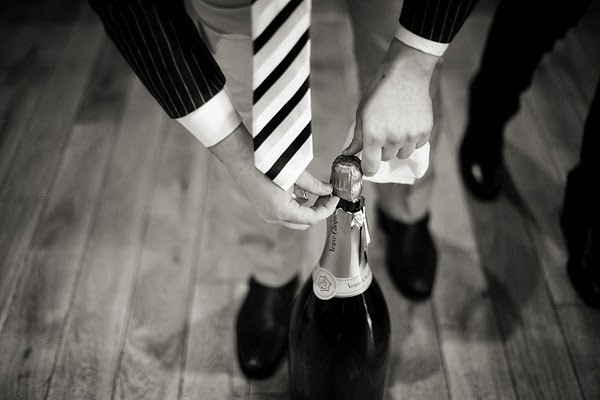 Wedding at London Rowing Club on the Thames. Opening a magnum of champagne