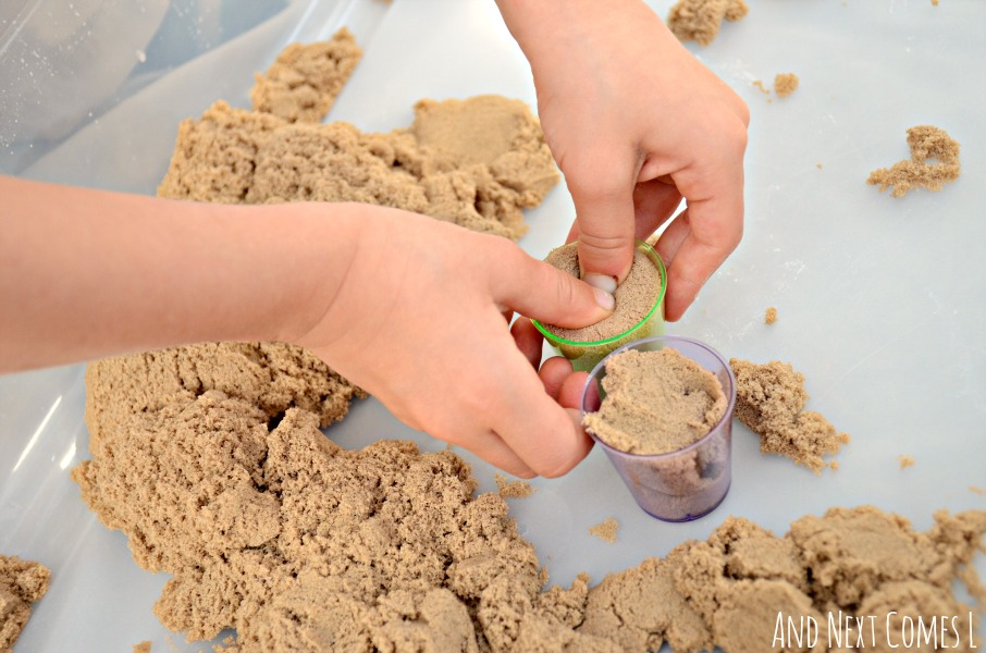 Fine motor sensory play for kids with kinetic sand and cups from And Next Comes L
