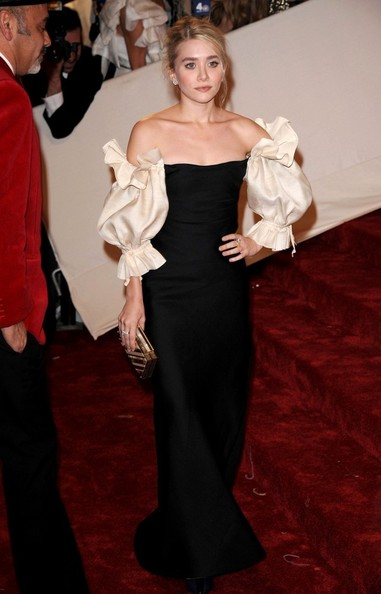Ashley Olsen in a vintage Christian Dior black column off-the-shoulder gown with puffy ivory peasant sleeves and a thigh-high slit at the 2011 MET Gala.