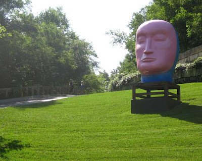 Huge pink head sitting on a green grass lawn