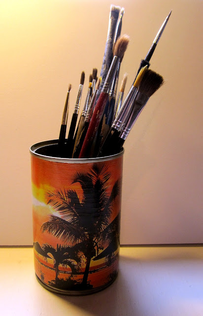 Recycling tin cans as pencil holders by decoupaging magazine pictures on them.