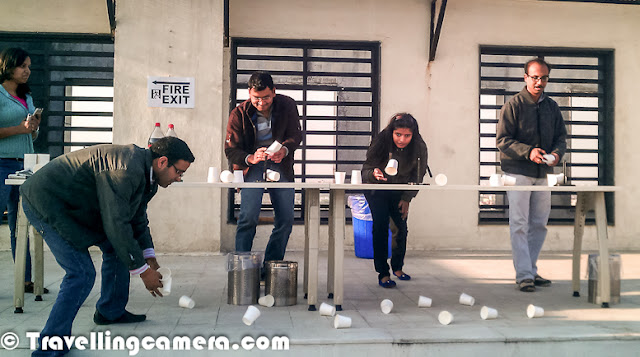 Every year we get last week off for Christmas and New Year celebrations. This year, before breaking for 10 days off, some of the folks in the group organized fun games on terrace of our office. All these photographs are clicked during the same with HTC Mobile Camera. Let's check out the PHOTO JOURNEY and try to understand about the games that happened...So here is the first game where three folks from each team are invited and game rules are briefed. Idea was to drop paper pieces into the dustbins you see in front. paper pieces can be rolled to make balls. Above photograph shows three participants deciding on the strategy to throw the ball, direction, consideration of air flow etc.It sounded easy but people had hard time to drop even a single paper ball into the dustbins. Unfortunately, it was very windy that day, which became a very good excuse for everyone :)Here is the next game. There is small pole in front of everyone and mutiple paper cups are given. One had to flip the cup from table in such a way that it rests on the top of the pole. This sounded impossible in the beginning, but people tried some creative ways to solve it. Although at the end, none of them was able to do it. Efforts were great and many attempts were quite close as well.There was another game, where two team members from one team had to participate. One of the them would get a company Logo. This person has to dictate the logo to second person through geometrical figures and some ways to connect them, but no hand/head movements. Second person had to draw this logo as person directions given by first person & whole team had to guess the Logo. This was competitively easy game and most of the folks did it, except the ones who got really tough Logo.There were few other team building games, where idea was to know more about people on the floor. But unfortunately all engineers applied complex algorithms to spoil it.