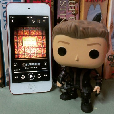 A small vinyl figure stands beside a white iPod with The Black Tulip's cover on its screen. The cover features a pattern of red and gold tiles with the title in the centre. The figure is done up as Hawkeye. he wears a black and purple leather outfit and carries a black bow.