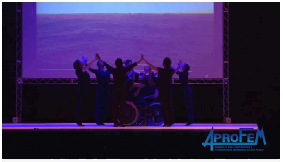 Descrição da Foto: Intérpretes estão no centro do palco, alguns de pé formando um círculo, mãos dadas e braços elevados em V, cabeça inclinada para atrás. Os outros estão dentro dançando livremente. Estão sobre um foco central com luz azul, com um telão no fundo com a imagem de nuvens.