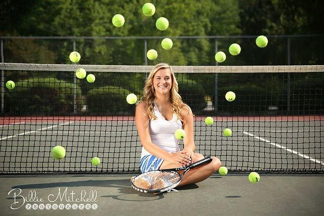 senior girl sitting in front of tennis net with tennis balls bouncing around her