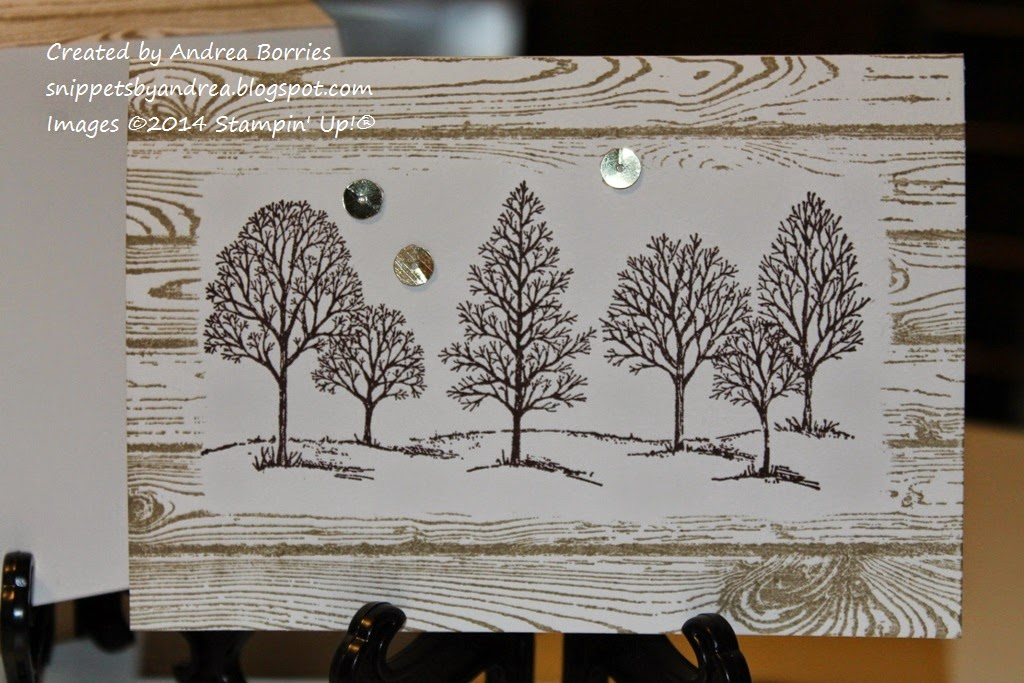 White card with an image of six trees stamped in dark brown in the middle. The trees are surrounded by a stamped hardwood frame in light brown. Embellished with three gold sequins.
