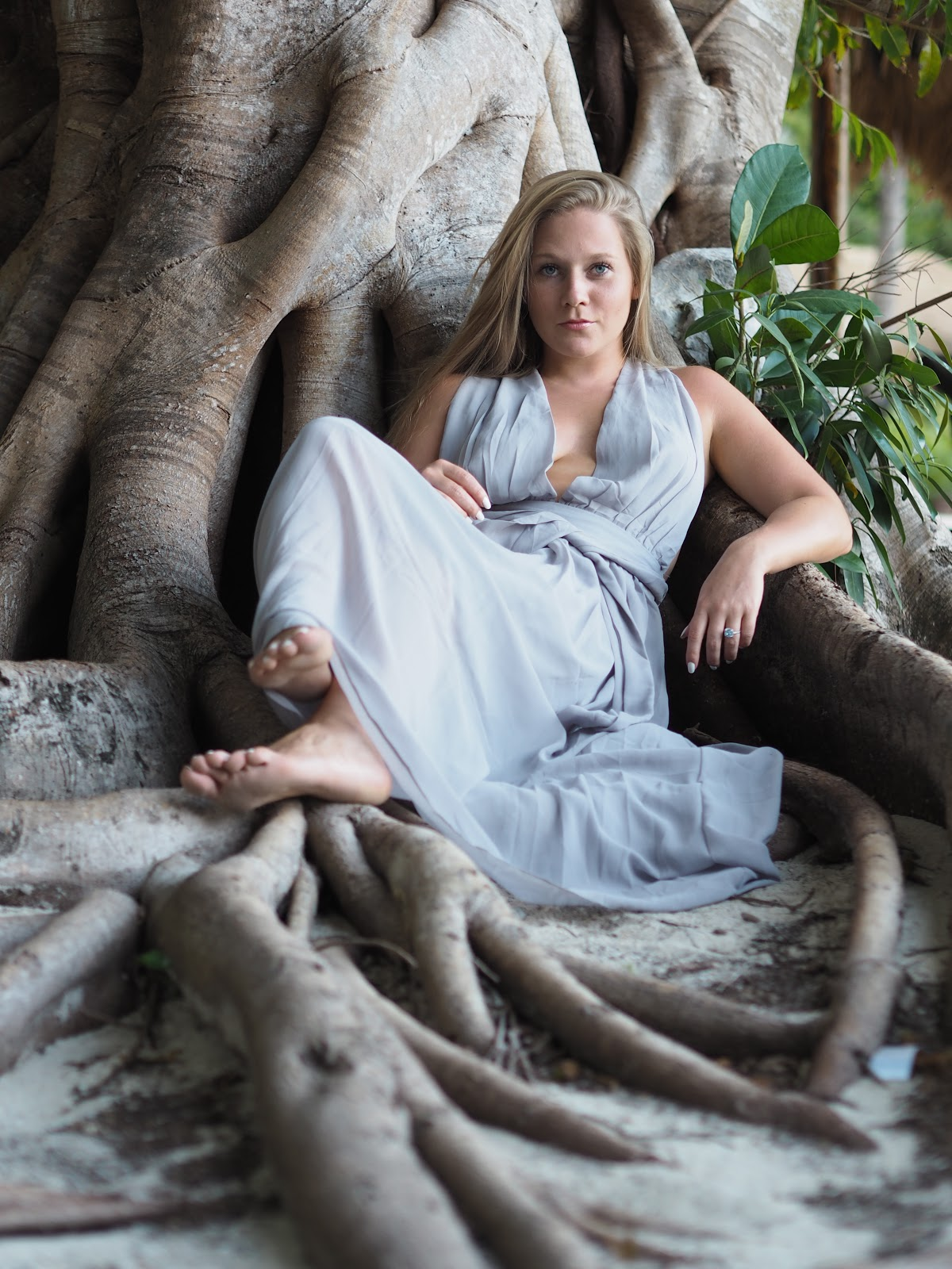 Katie Matthews, Blonde Girl wearing Grey dress and sitting under huge tree roots