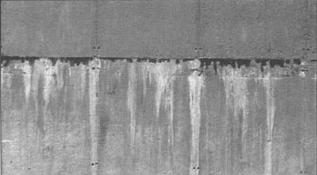 Detalle de una junta mal ejecutada en un muro de hormigón.