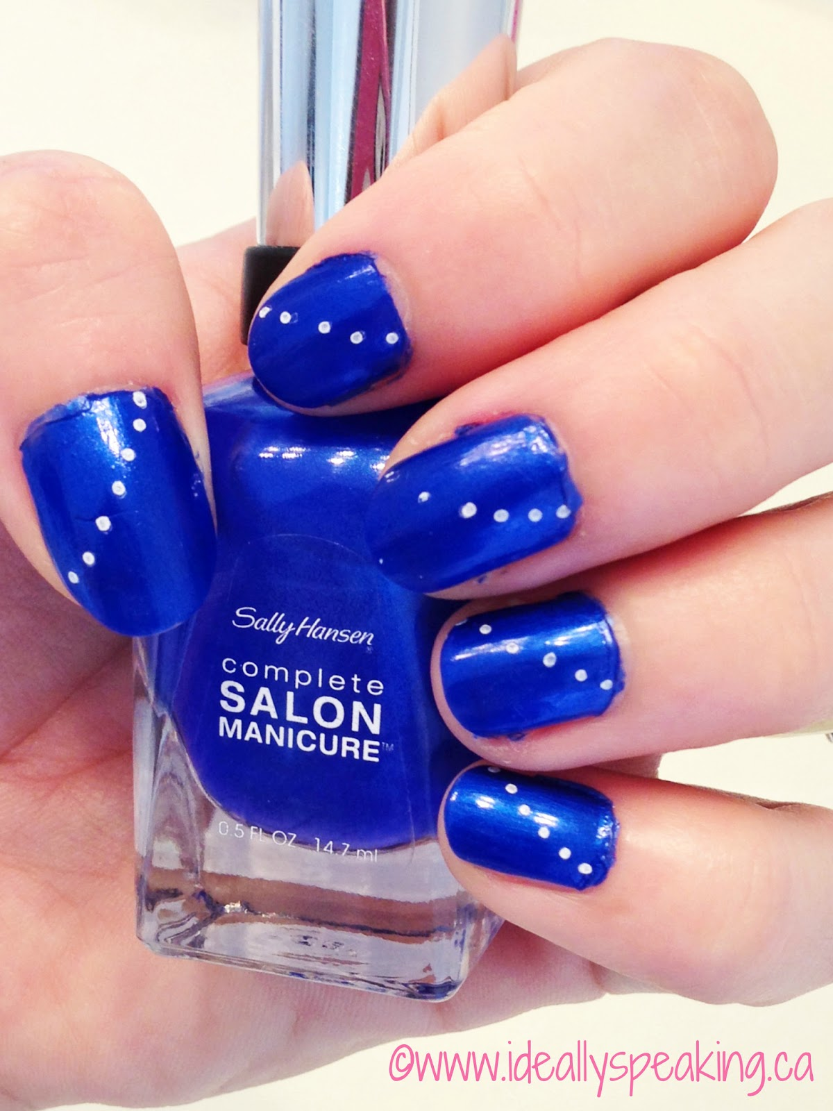 Electric blue nails with white polka dots.